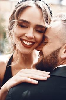 Mulher feliz com lábios vermelhos impressionantes abraça seu homem barba