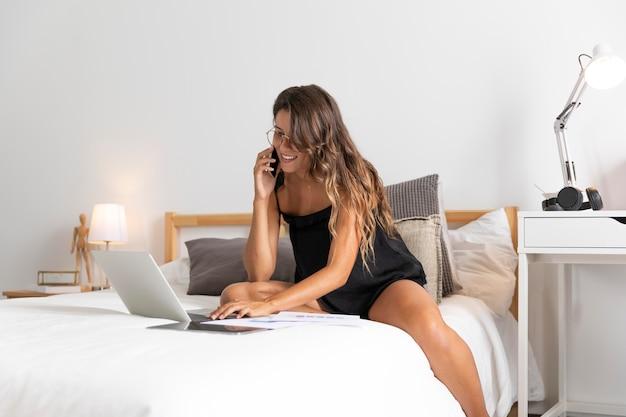 Mulher feliz com laptop na cama falando ao telefone