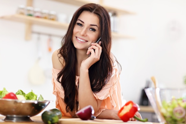 Mulher feliz com legumes na cozinha moderna