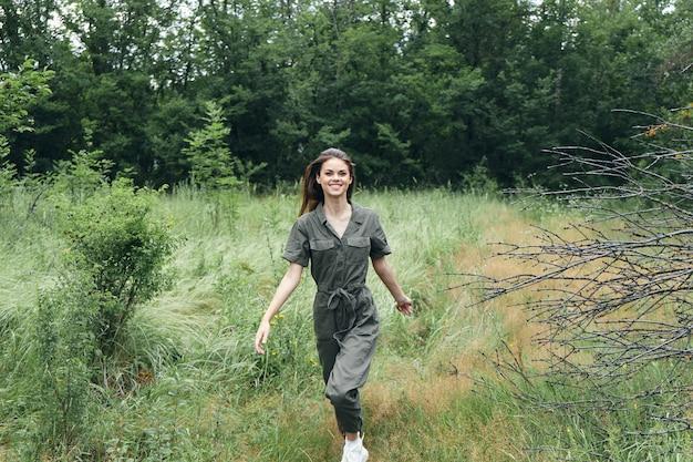 Mulher feliz com macacão verde corre no prado na natureza na floresta