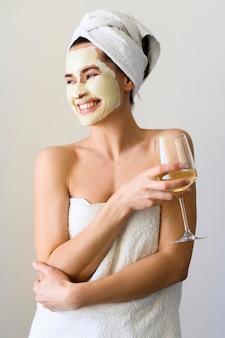 Mulher feliz com máscara facial, desfrutando de copo de vinho