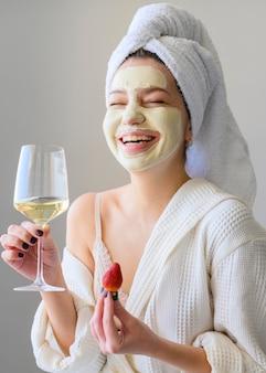Mulher feliz com máscara facial segurando copo de vinho e morango