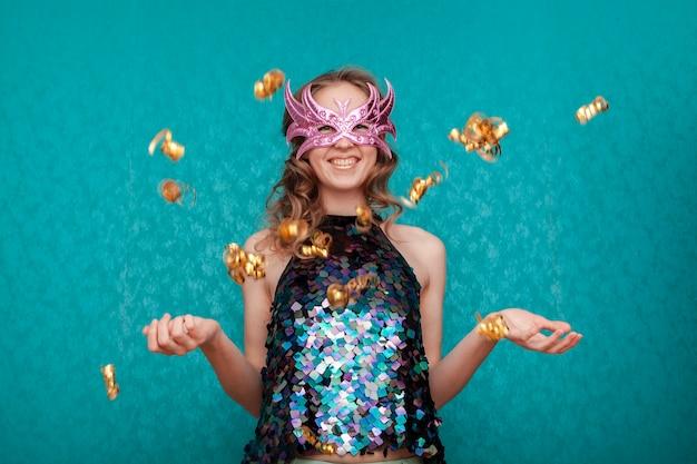 Mulher feliz com máscara rosa e confetes dourados
