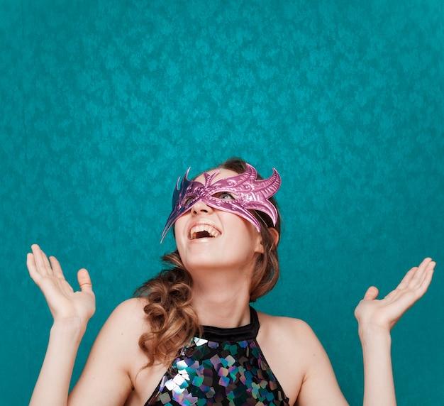 Mulher feliz com máscara rosa ri