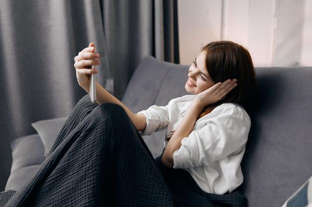 Mulher feliz com o celular no sofá e manta cinza ajoelhada para descansar