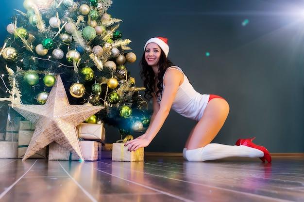 Mulher feliz com o presente debaixo da árvore de natal. jovem garota sexy em lingerie e boné de papai noel coloca um presente de natal. preparando-se para o feriado. luzes brilhantes na árvore de natal.