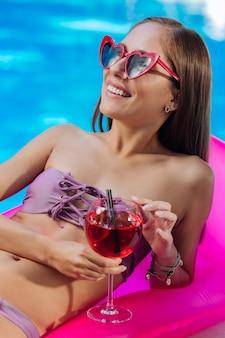 Mulher feliz com óculos de sol vermelhos tomando banho de sol enquanto estava deitada no colchão de ar na piscina