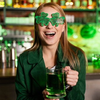 Mulher feliz com óculos de trevo comemorando st. dia de patrick no bar