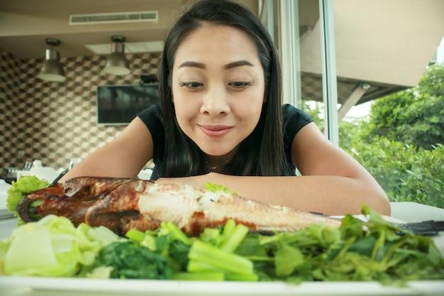 Mulher feliz com olhar da cara do wow em peixes grelhados.