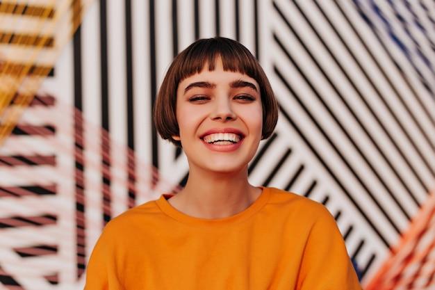 Mulher feliz com penteado curto sorrindo amplamente na parede listrada
