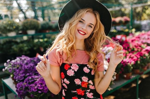 Mulher feliz com penteado encaracolado, posando em laranjal. espectacular modelo europeu ao lado de flores.