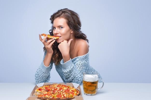 Mulher feliz com pizza e cerveja na parede cinza