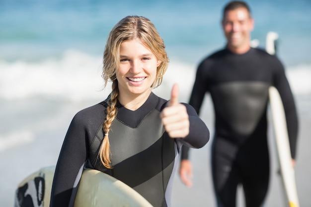 Mulher feliz com prancha de surf aparecendo o polegar
