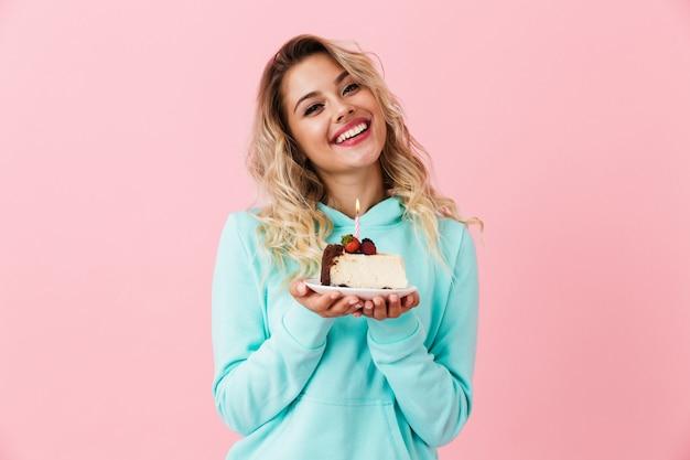 Mulher feliz com roupas básicas segurando um pedaço de bolo de aniversário com uma vela, isolada sobre uma parede rosa