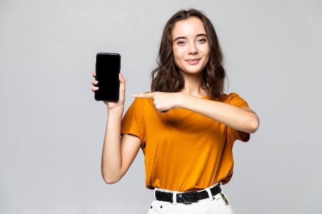 Mulher feliz com roupas casuais, mostrando a tela do smartphone em branco sobre a parede cinza