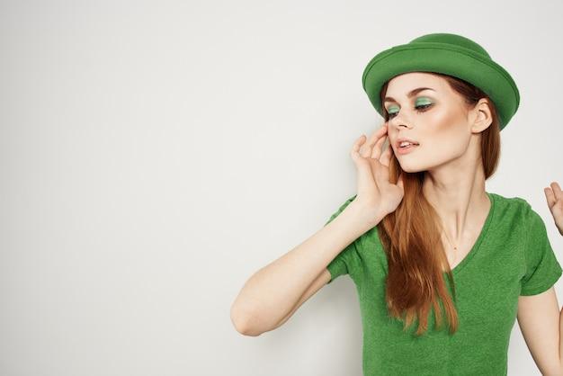 Mulher feliz com roupas verdes em modelo de maquiagem de chapéu de trevo do dia de são patrício
