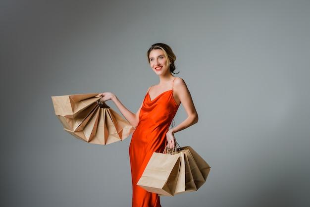 Mulher feliz com sacolas de compras contra um fundo cinza natal ou black friday