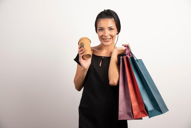 Mulher feliz com sacolas de compras e café em pé na parede branca.