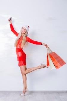Mulher feliz com sacos de compras e telefone