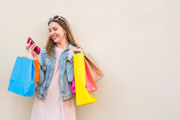 Mulher feliz com sacos de compras usando smartphone