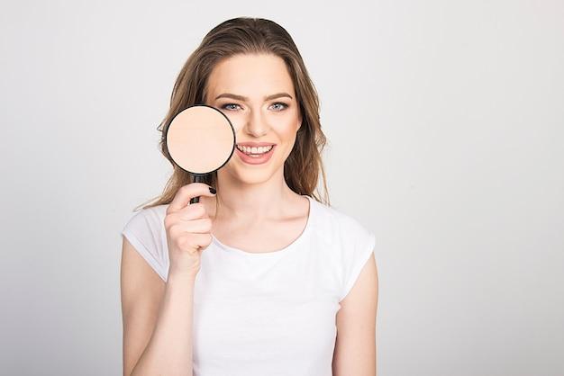 Mulher feliz com seu conceito de cuidado de pele de beleza de pele limpa e saudável. mulher segurando a lupa para o rosto, mostrando a pele limpa.