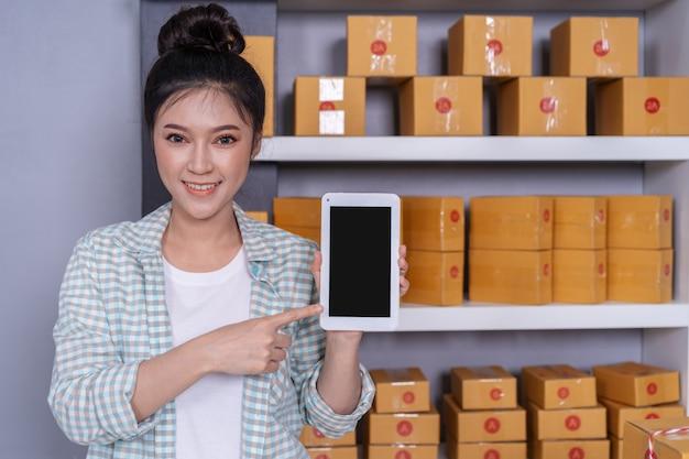 Mulher feliz com seu tablet digital e caixa de encomendas de correio no escritório em casa