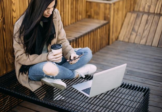 Mulher feliz com smartphone e laptop no centro da cidade