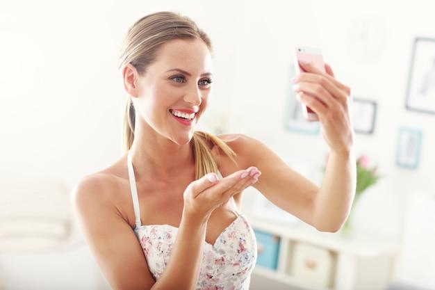 Mulher feliz com smartphone em casa