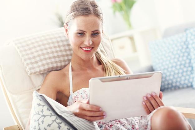 Mulher feliz com tablet em casa