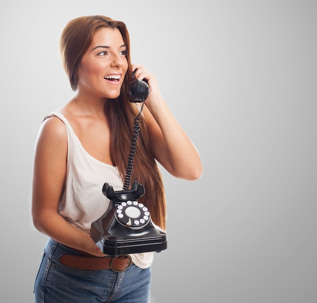 Mulher feliz com telefone fixo e telemóvel