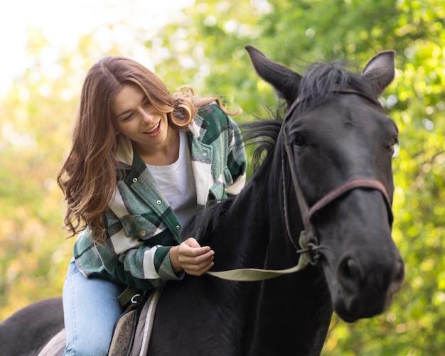 Mulher feliz com tiro médio andando a cavalo