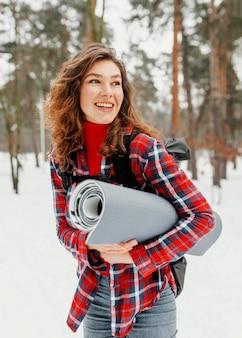 Mulher feliz com tiro médio carregando tapete