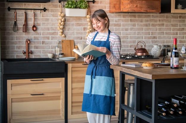 Mulher feliz com um avental de linho em pé na cozinha à mesa com um sorriso folheando um livro de receitas