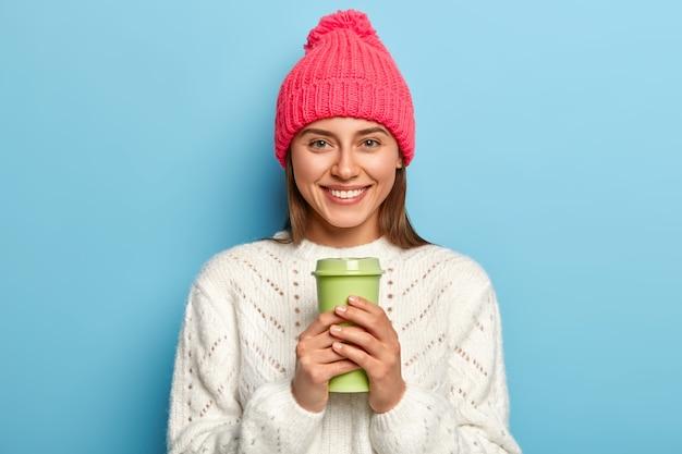 Mulher feliz com um chapéu rosa brilhante e um suéter branco quente, segurando uma xícara de café para viagem, posa contra a parede azul