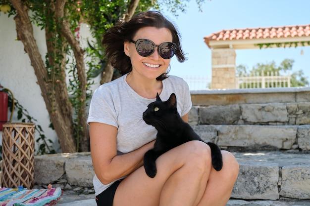 Mulher feliz com um gato preto, retrato ao ar livre do proprietário e do animal de estimação.