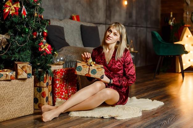 Mulher feliz com um presente mágico perto da árvore de natal em casa