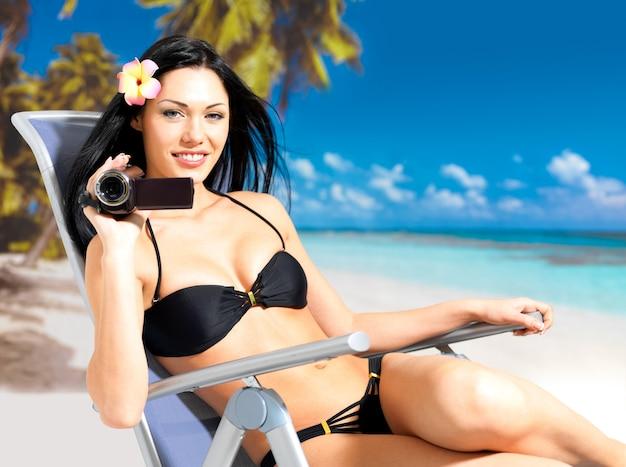 Mulher feliz com uma câmera de vídeo na praia