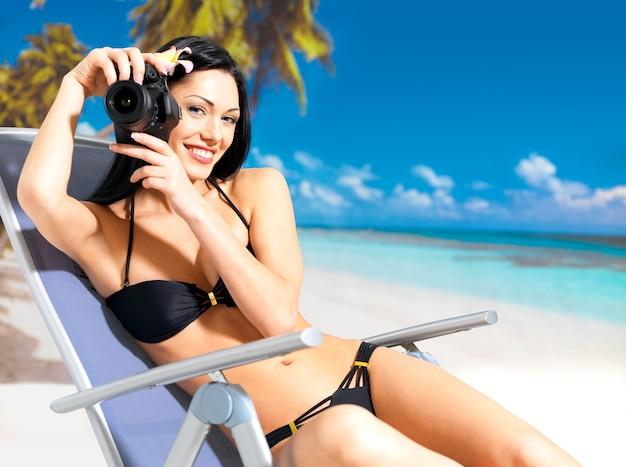 Mulher feliz com uma câmera digital tirando fotos na praia