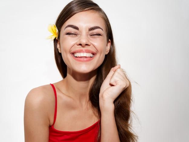 Mulher feliz com uma flor amarela no cabelo rindo retrato closeup