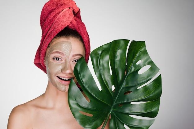 Mulher feliz com uma toalha na cabeça aplica uma máscara de limpeza no rosto e segura uma folha grande