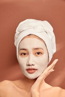 Mulher feliz com uma toalha na cabeça aplica uma máscara de limpeza no rosto