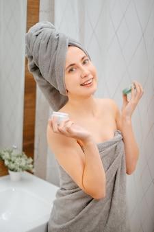 Mulher feliz com uma toalha na cabeça está de pé no banheiro com um pote de creme. conceito de cuidados com o corpo.