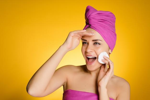 Mulher feliz com uma toalha na cabeça remove a maquiagem com um disco de algodão em um fundo amarelo