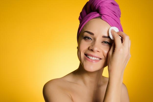 Mulher feliz com uma toalha na cabeça remove a maquiagem da pele