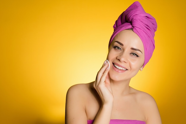Mulher feliz com uma toalha na cabeça removeu a maquiagem com um disco de algodão