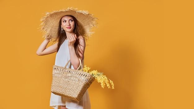 Mulher feliz com vestido branco de verão e chapéu de palha com ramo de flores na bolsa