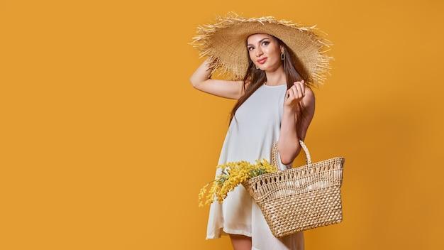 Mulher feliz com vestido branco de verão e chapéu de palha com ramo de flores na bolsa Foto Premium