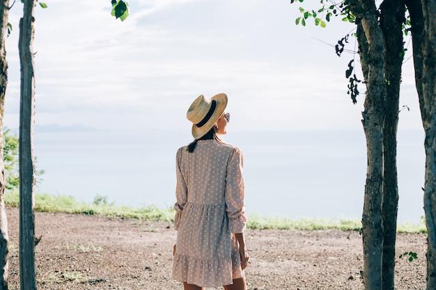 Mulher feliz com vestido fofo de verão e chapéu de palha nas férias com vistas tropicais exóticas
