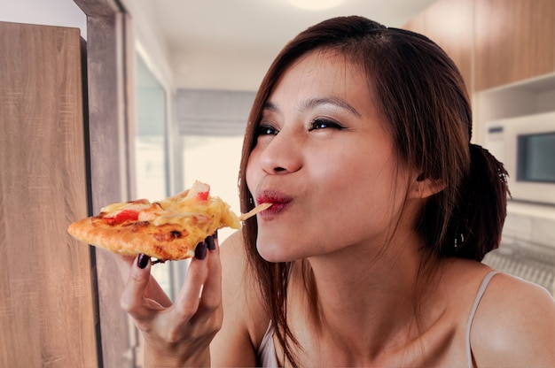 Mulher feliz comendo pizza saborosa.