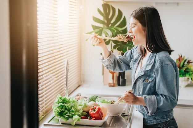 Mulher feliz comendo salada de legumes frescos saudáveis na cozinha